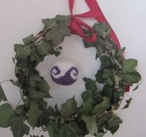 Gestrickte Weihnachtskugel im Efeukranz