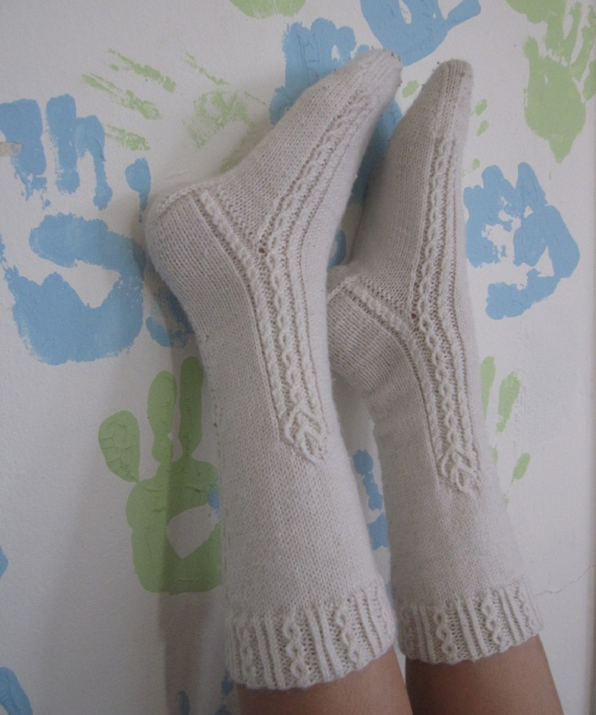 Weiße, handgestrickte Socken mit traditionellen Zugmaschenmodeln