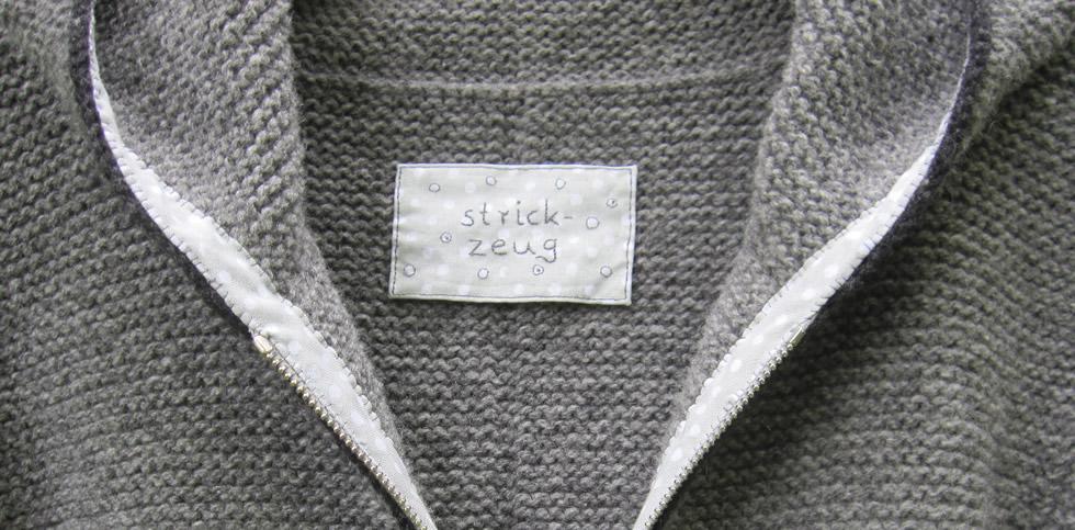 Trachtenjacke mit Kapuze, Detail mit Label, Reißverschluss und Schrägband