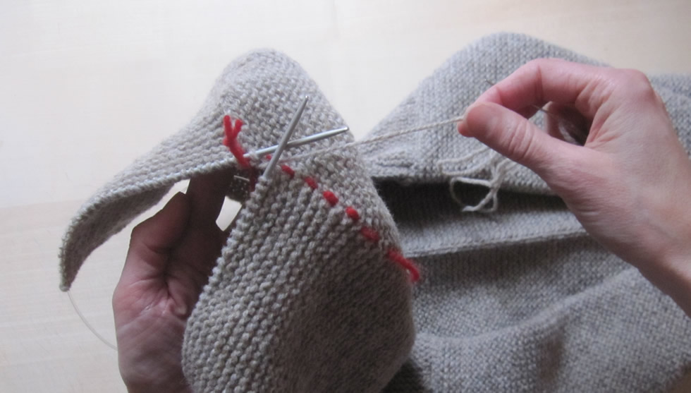 Grafting knit stitches together to form a hood with an invisible seam